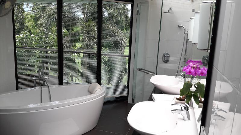 Deep bath, glass shower cubicle, twin basins