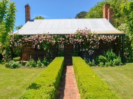 Climbing roses and clipped box hedges welcome guests to the front of the cottage.