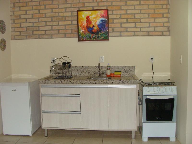 Cozinha totalmente equipada com talheres, panelas e pratos.