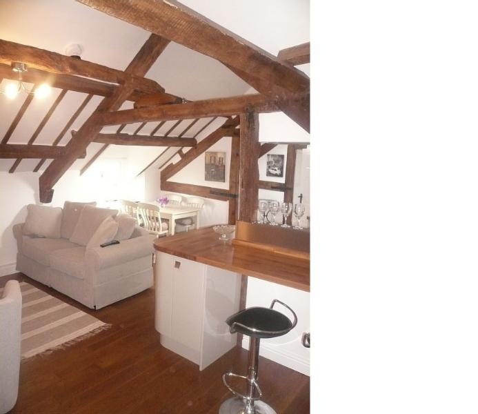 Deze foto toont de open lounge / eetkamer met balken in de gewelfde plafond