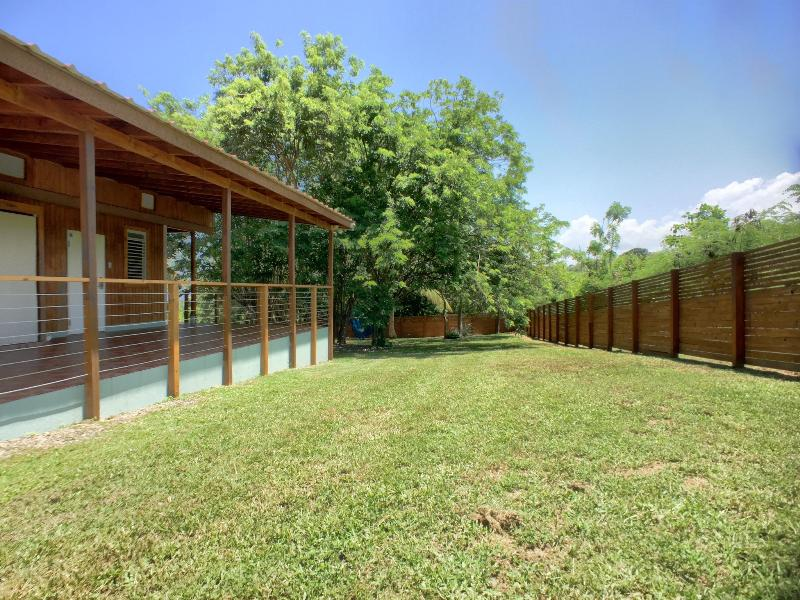 Large backyard enclosed by wooden fence.
