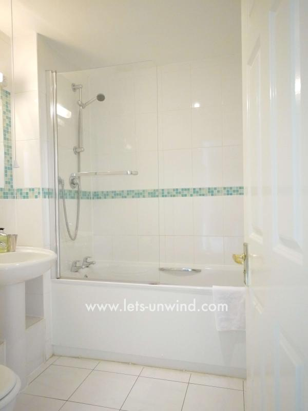 The bathroom is bright and clean and has a bath with thermostatically controlled shower over.