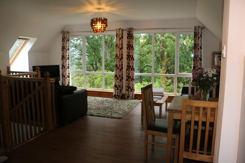 Living / dining area with views out to the gardens and landscape beyond