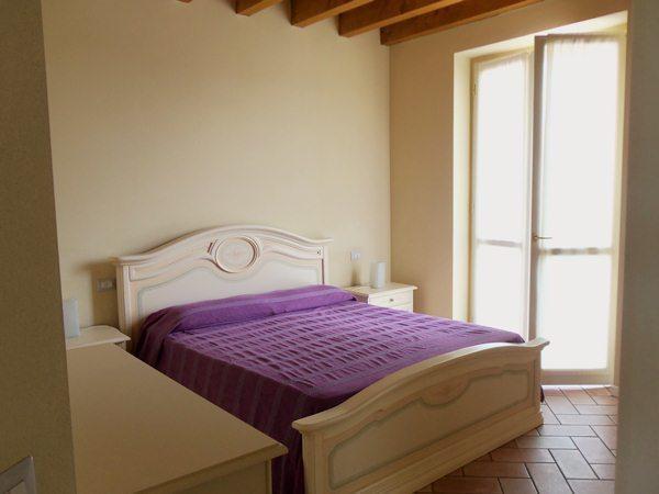 Camera da letto matrimoniale che conduce al balcone