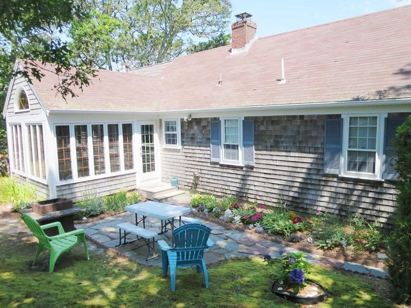 Exterior- Back of seaside cottage with patio and charcoal bulit in grill and small table - 11 Marshview Road Chatham Cape Cod New England Vacation Rentals