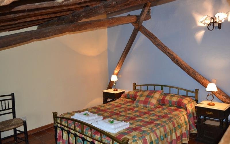 Habitación abuhardillada con cama doble de matrimonio con cabecero hecho con las vigas del techo.