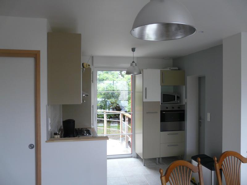 La cuisine dispose d'un accès sur la terrasse exposée plein sud. accessible par fauteuil.