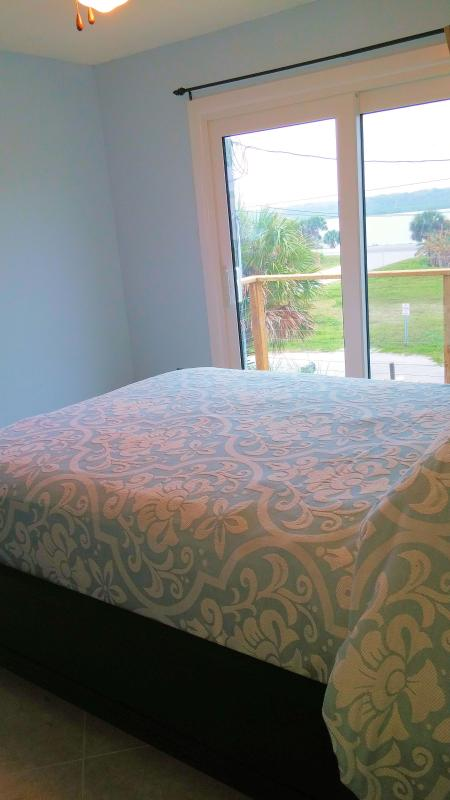 2nd bedroom with top of the line queen bedding and adjoining sunset deck with view of Indian River