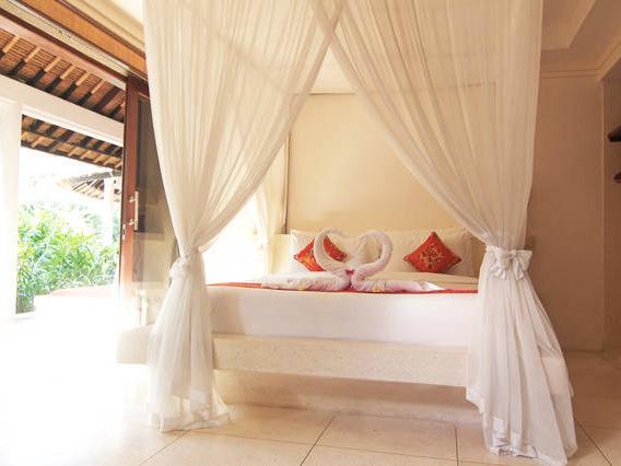 Une literie de qualité avec des draps de luxe et moustiquaire pour un sommeil confortable.