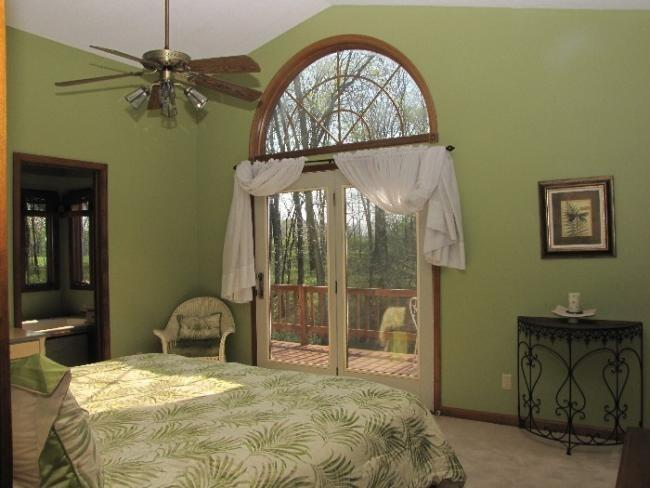 Master Bedroom with King bed, doors to wrap around deck with table and chairs for morning coffee/tea