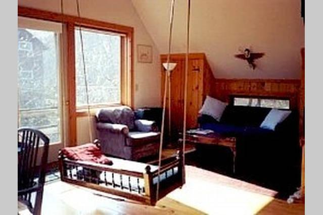 Sunlight warms the main living space - the swingseat holds 3 adults. Hardwood floors throughout