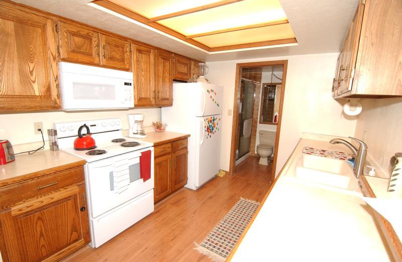 Cuisine entièrement équipée avec salle de bains adjacente invités.
