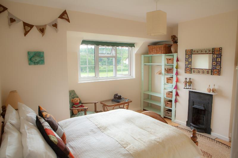 master double bedroom with original fireplaces, wooden floors and views over Dorset countryside
