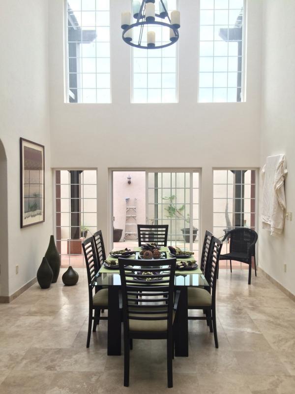 Sala da pranzo che si apre alla cucina e zona pranzo all'aperto