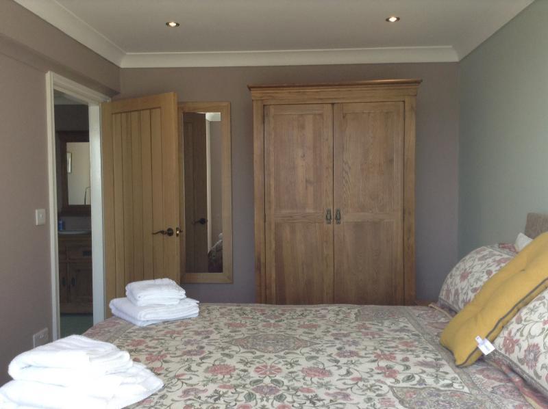 Quarto com cama de casal grande armário, mesas de cabeceira e luzes de toque, gavetas sob a cama e robe