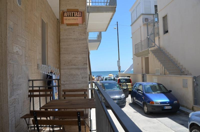 The small balcony overlooking the sea side of the house with a small table , chairs and awning
