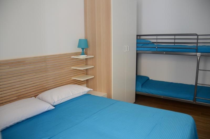 Comfortable, functional and bright bedroom with a double bed and a bunk bed