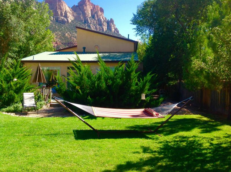 A large, grassy yard with a new hammock, parking for 6 cars, front deck and BBQ grill