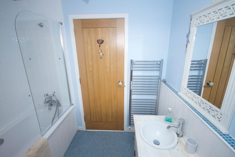 Badezimmer mit elektrischer Dusche über der Badewanne