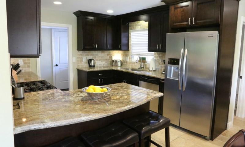 Partial open concept kitchen with granite counter tops and stainless steel appliances