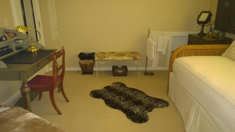 From left to right, fancy chair, fully stocked desk, luggage bench, towel rack, dresser & twin beds.