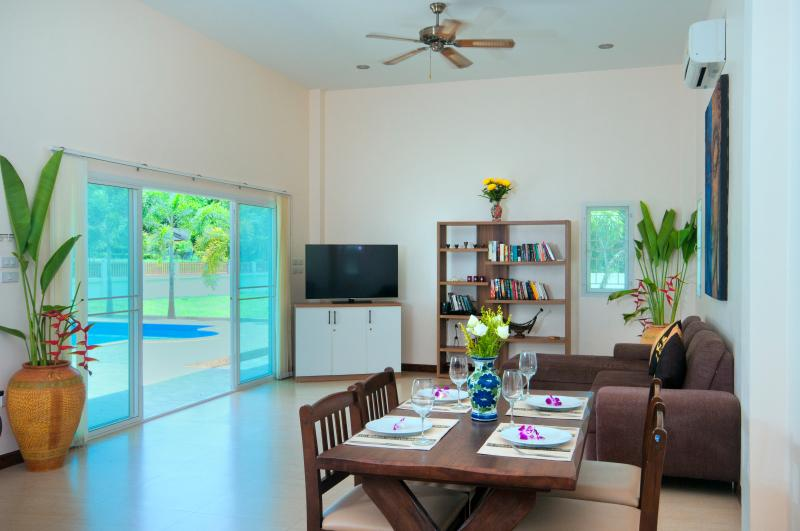Spacious dining and living area with large sliding doors and views to the pool and garden.