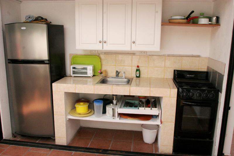 Cuatro quemadores de la estufa, ollas, sartenes, platos de colores, tazas fre, platos de servir, una nevera. y el congelador.