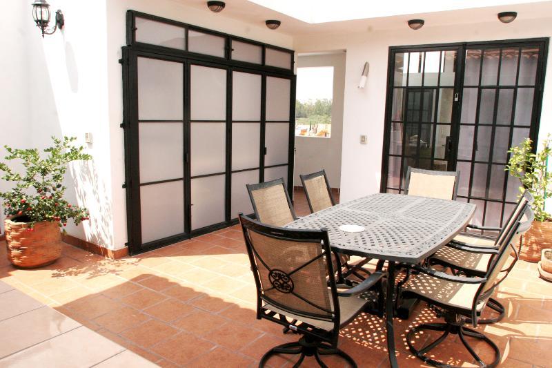 sillas giratorias alrededor de la mesa grande con habitaciones contiguas que se abren a la terraza.