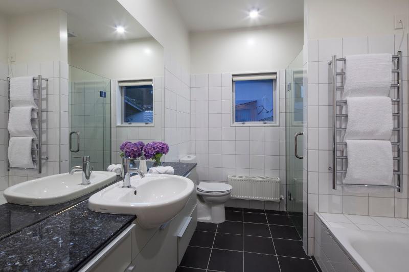 Drie badkamers met luxe toiletartikelen en haardrogers