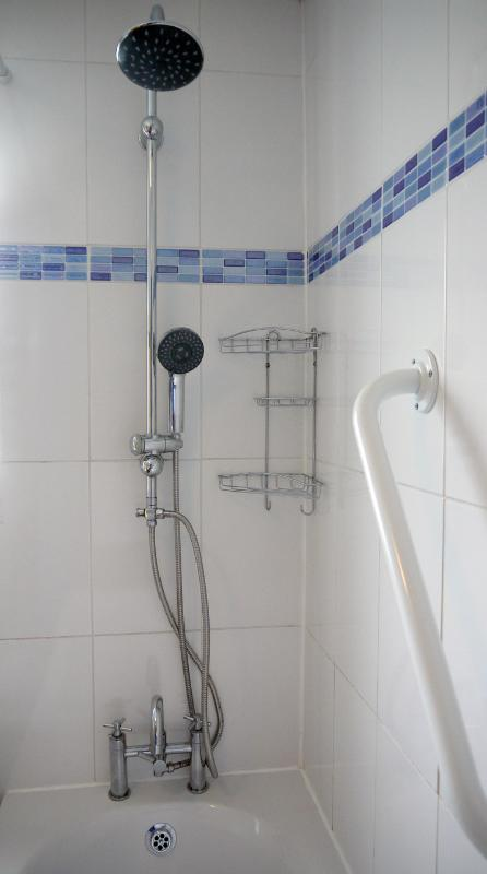 Tiled bathroom has a shower over the bath