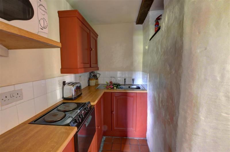 The kitchen is galley style, with a solid stone wall to one side, and quarry tile flooring