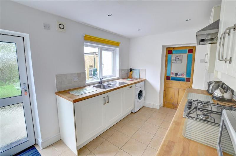 Thet fitted kitchen includes a dishwasher, washing machine and has a door to the patio