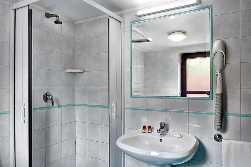 The bathroom is off the kitchen and is decorated with clean, crisp white tiles.