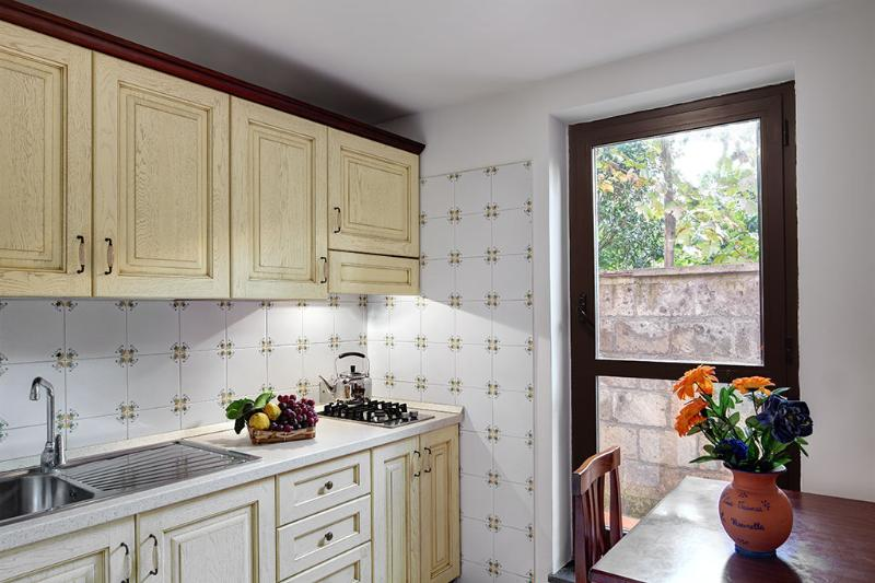 A modern kitchenette, equipped with two electric rings, a fridge and a freezer, toaster and Italian