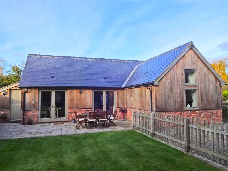Unique and stylish cedar and slate bungalow with french doors, private enclosed garden and parking