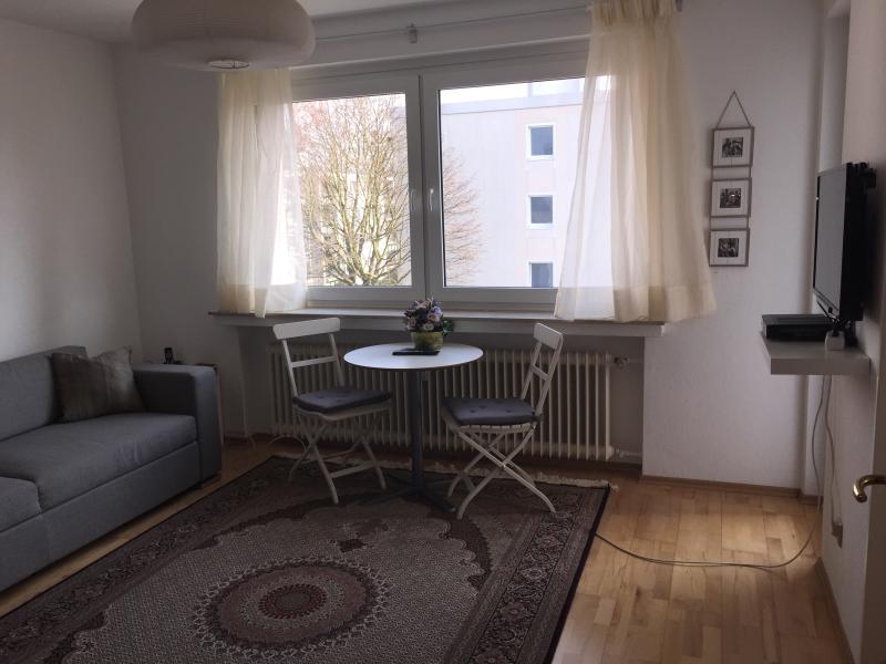 Pequeña mesa de comedor con dos sillas en la sala de estar, ventanales