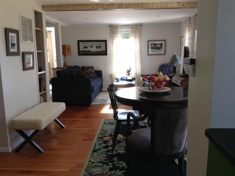 Area di soggiorno-pranzo open concept con opere d'arte locali e televisore a schermo piatto.