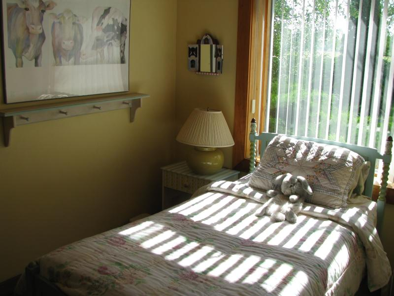 Single bedroom with view over lawn and cow pasture