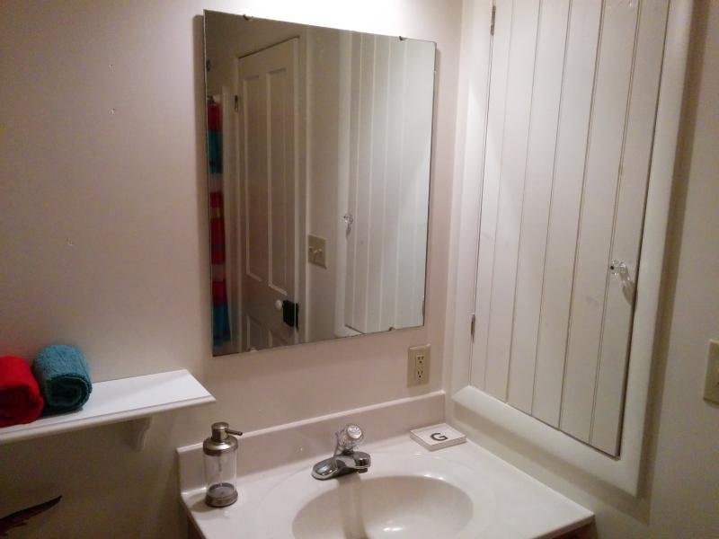 Full bathroom upstairs, towels provided. Sink with additional towels in cupboard to right.