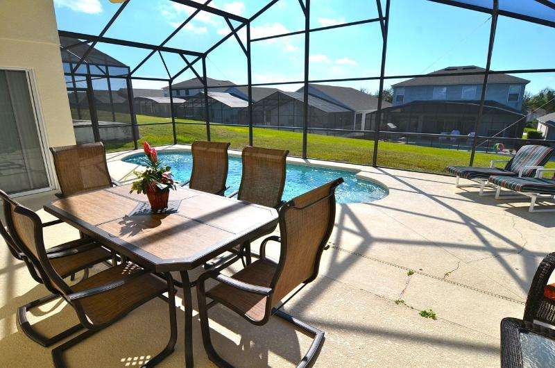 Spacious pool deck with shaded dining area