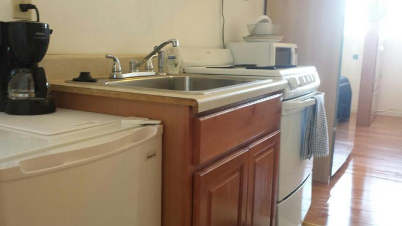 small kitchen, stove oven, microwave, refrigerator, cook wear, cups, and more.