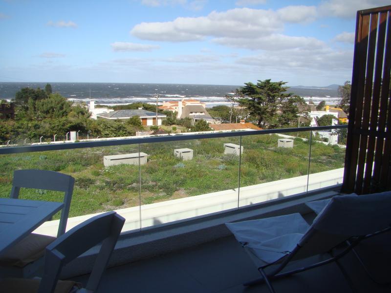 el balcon con reposeras y mesa