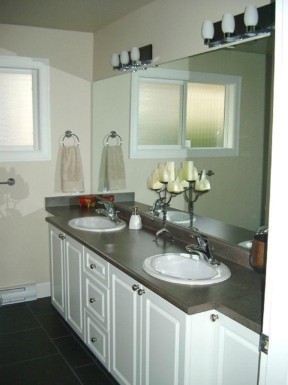 main level second bathroom w/ under-floor heating, tub, shower and double wash basins