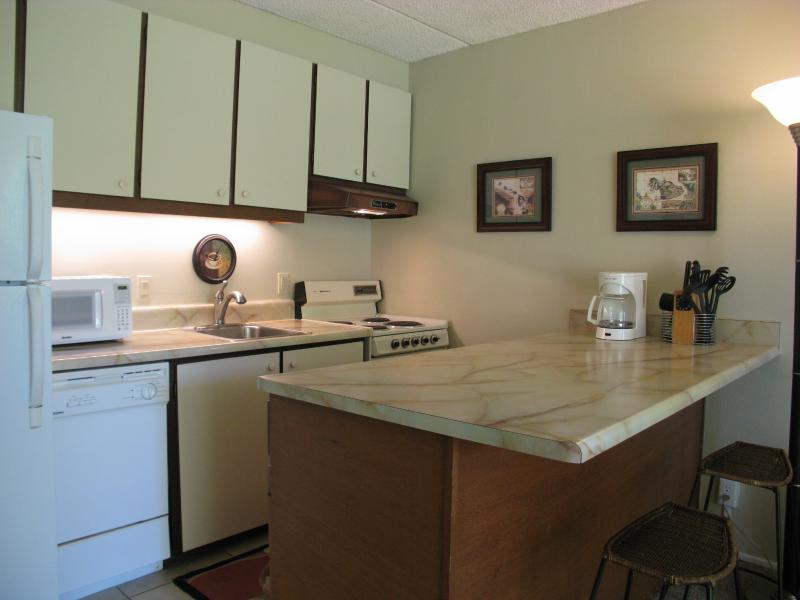 Kitchen area with breakfast bar, oven, refrigerator, dish washer, garbage disposal, coffee maker.
