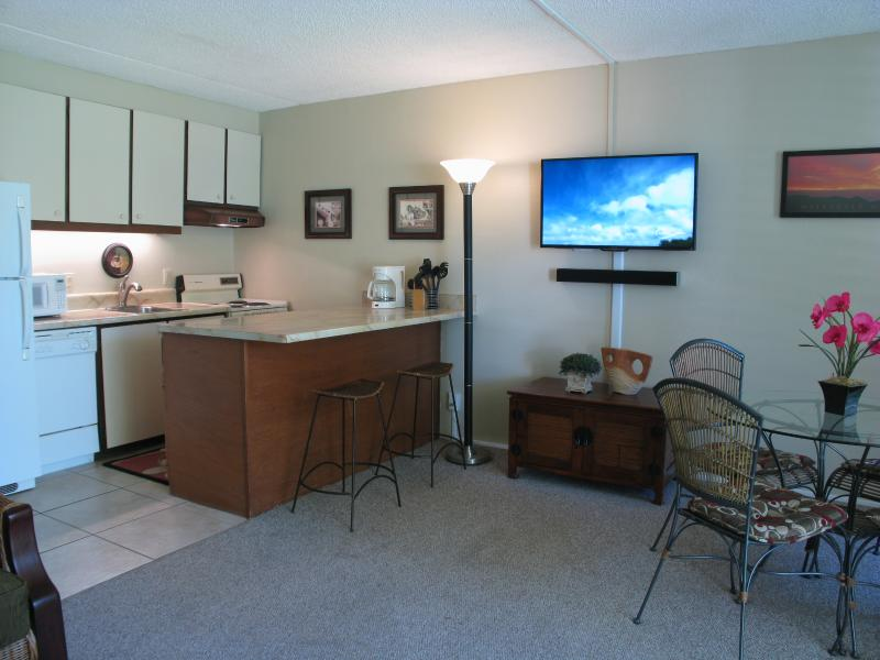 Open kitchen, living, dining room area. Tiled kitchen w/ breakfast bar & plenty of cooking utensils.
