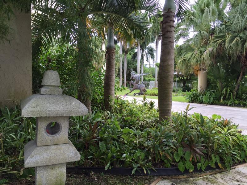 Pagode de pedra fica por palmeiras e a escultura de bronz pé 12 Centaux por Nicole Taillon