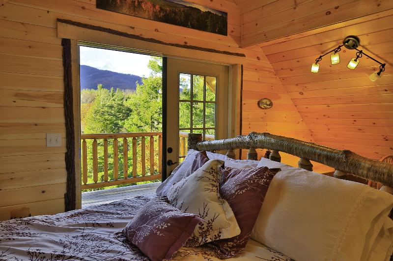 Master bedroom with yellow birch bed, and views out the door to balcony