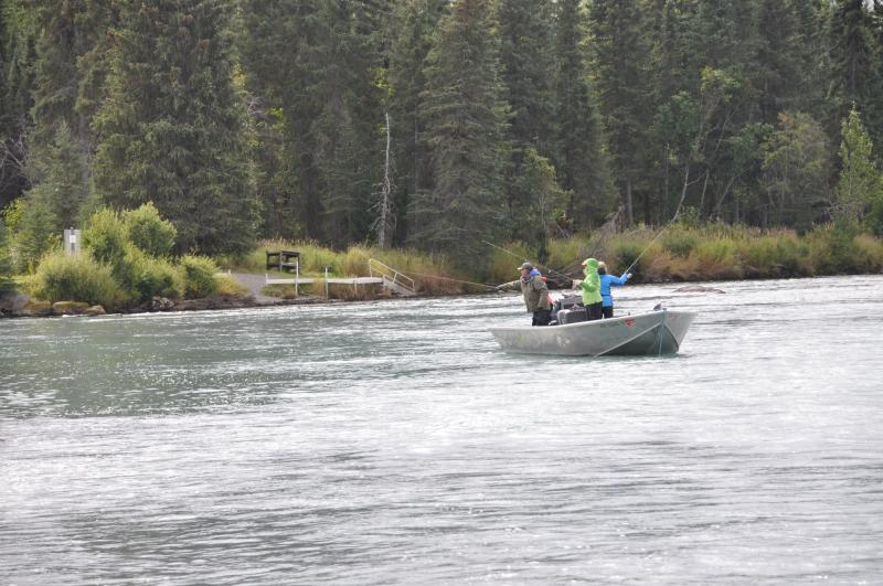 People fishing on a boat down stream from our homestead