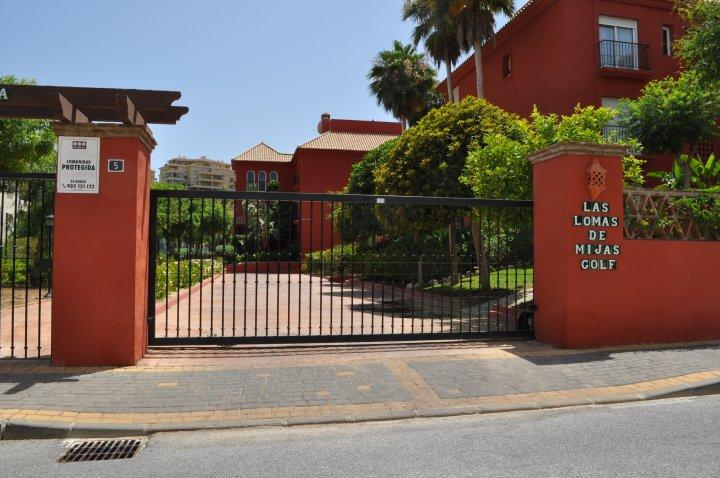 The gated entrance to Las Lomas and the underground car park with elevator access to the apartment