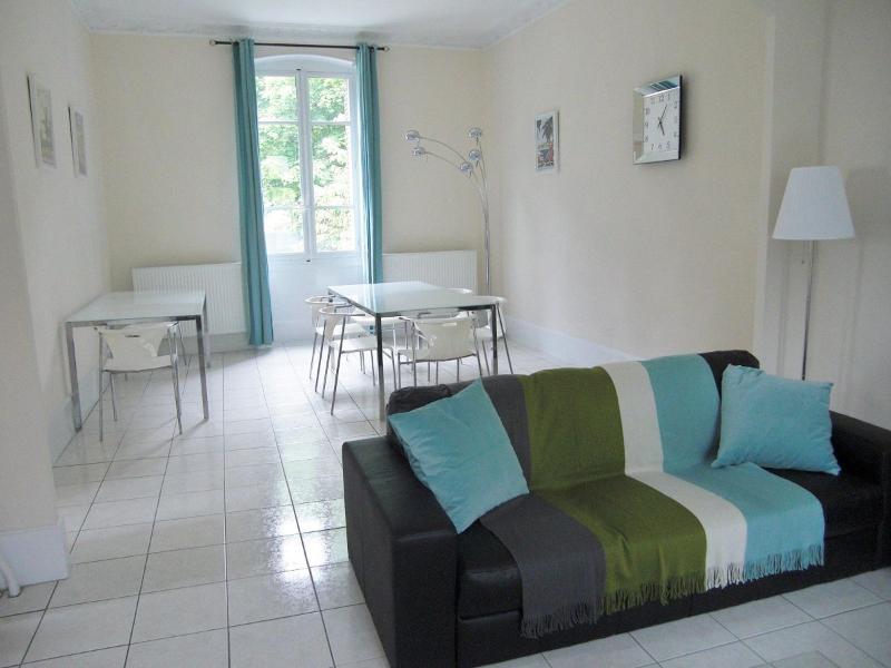 Leve e confortável sala de jantar, com duas mesas de jantar, dois sofás, televisão e fogo a lenha.